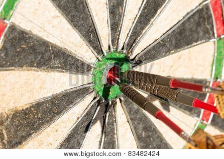 Darts board with 3 arrows in bullseye