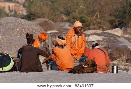 Indian Sadhus Siting On The Beach Near River Ganga