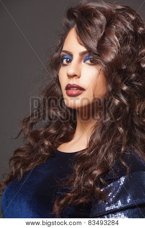 beautiful indian woman with curly hair in blue dress