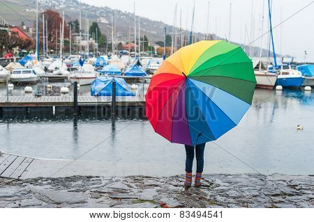 Child under big colorful umbrella watching the rain on the lake, view from the back