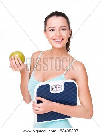 Fit beautiful woman holding weighs and apple
