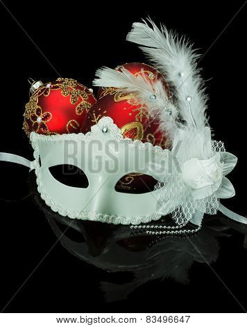 White Mask And Christmas Red Balls On A Black Background