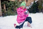 image of snowball-fight  - Little cute girl standing on one knee in the snow with a snowball in her hands - JPG