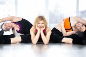 foto of do splits  - Sporty attractive middle aged woman with her friends in fitness class sitting in splits doing stretching sport exercises with dance elements - JPG