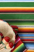 stock photo of sombrero  - Mexican background with sombrero straw hat maracas and traditional serape blanket or rug - JPG