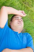pic of bald headed  - Stressful fat man is lying on the green grass with arm on his head - JPG