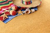 stock photo of mexican  - Mexican beach background with sombrero straw hat traditional serape blanket starfish seashells and maracas - JPG