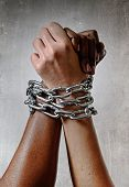 pic of chains  - white Caucasian hand chained with iron chain and locked together with black ethnicity female around wrists in togetherness multiracial respect and understanding concept - JPG