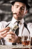stock photo of suspenders  - Gangster in shirt and suspenders is counting money and smoking Cuban cigar while sitting at the table - JPG