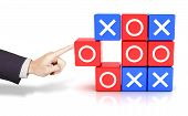 stock photo of tic  - Composite image of hand pushing a circle to win the tic tac toe game - JPG