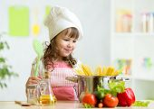 picture of cook eating  - Cook kid girl makes healthy vegetables meal in the kitchen - JPG