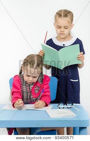 Teacher Standing Behind The Pupil Looks Notebook