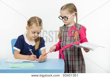 The Teacher Points To A Pointer In The Notebook Student