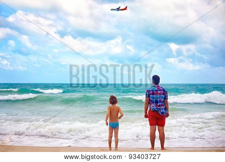 Father And Son Standing On Beach At Stormy Weather, Watching The Plane Fly