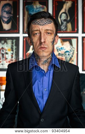 Tattoo Master In Black Jacket And Blue Shirt In Studio