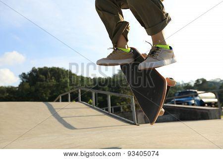 skateboarder legs doing heelflip at skatepark