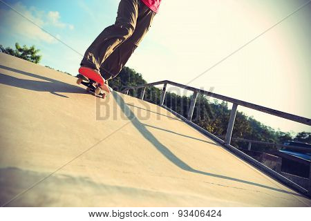 skateboarder legs riding skateboard at skatepark ramp,vintage effect