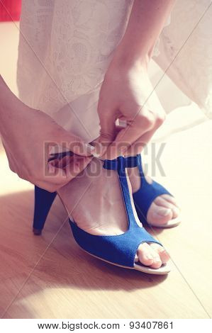 Close Up View Of Woman Putting Blue Shoe On