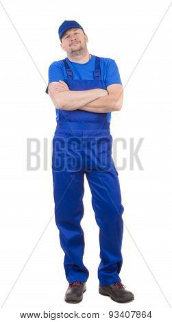 Man in blue overalls with hands crossed.