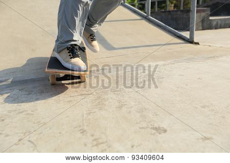 skateboarder legs riding skateboard at skatepark ramp