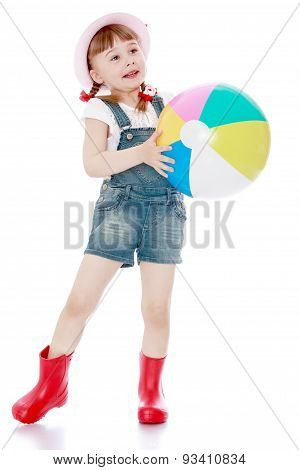 Cheerful girl in short summer shorts and boots holding a large s