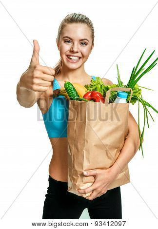 Young Athletic Woman Gesturing Thumb Up With Grocery Bag Full Of Healthy Fruits And Vegetables