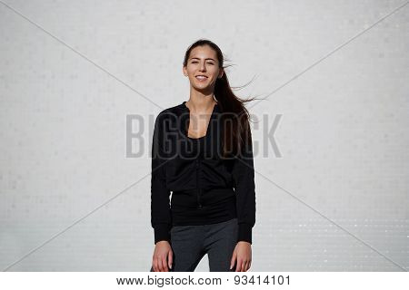 Portrait of smiling fit and healthy woman standing outdoors on white wall background  athletic