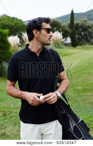 Portrait of wealthy golf player man standing on beautiful golf course looking away