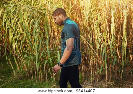 Half length portrait of athletic dark-skinned man having a rest after workout while walking outdoors