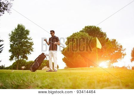 Handsome mature man playing golf at beautiful summer day on green course