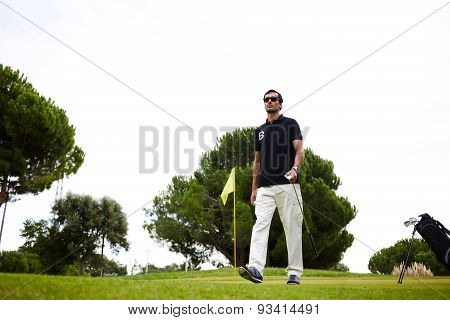 Full length portrait of professional golf player walking to the next hole in golf