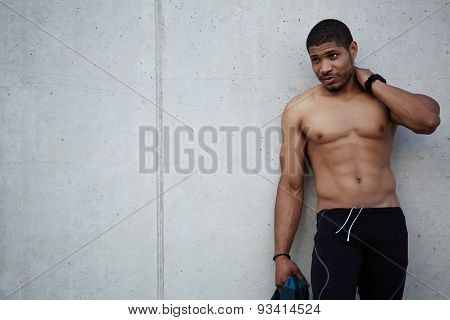 Portrait of handsome fit man with defined muscular chest and abdominal standing at copy space