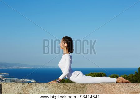 Young woman seeking enlightenment through meditation stretching exercise yoga pose at sunny day