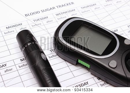Glucometer And Lancet Device On Empty Medical Forms For Diabetes
