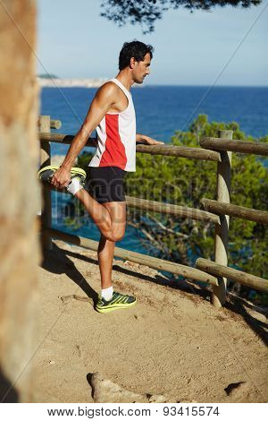 Athletic man enjoy the view while doing stretch exercise before a jog at sunny evening