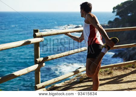 Athletic man enjoy the view while doing stretch exercise before a jog