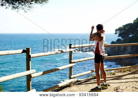 Young runner stretching hands while standing on the edge of a cliff near the ocean