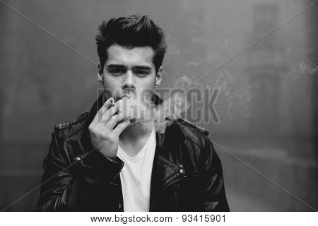 Trendy attractive man blowing smoke out of his mouth while leaning on a gray wall