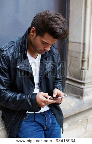 Portrait of young charming man using busy smart phone while chatting with someone