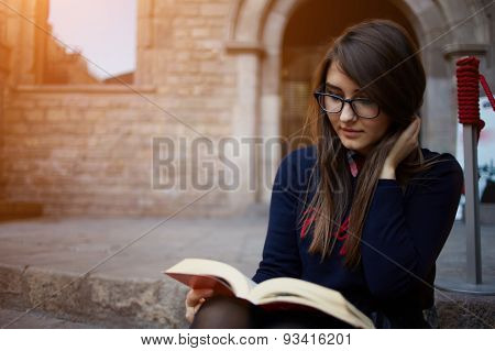 Charming teenager spectacled sitting outdoors with open book and absorbs knowledge