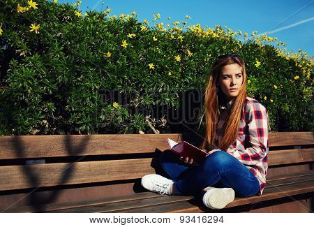 Beautiful student relaxing in the park after college while reading a book outdoors