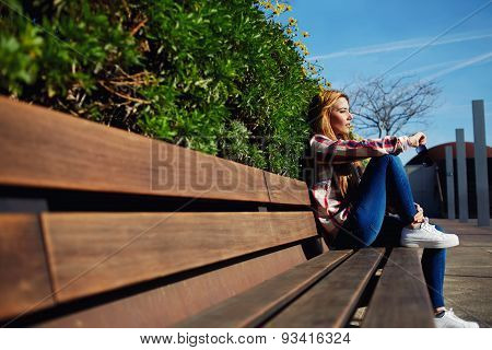 Charming young girl relaxing in the spring park enjoying nature in sunny day outdoors