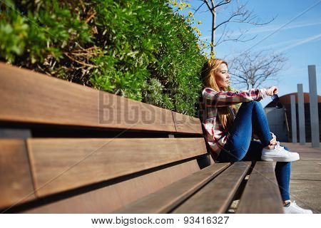 Female student relaxing at campus during her class break while sitting in the park