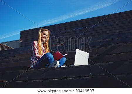 Shot of smiling college student studying with a book and laptop computer at campus
