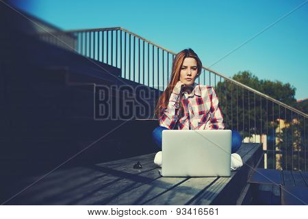Young mysterious woman learn with laptop computer and enjoying sunny day outdoors