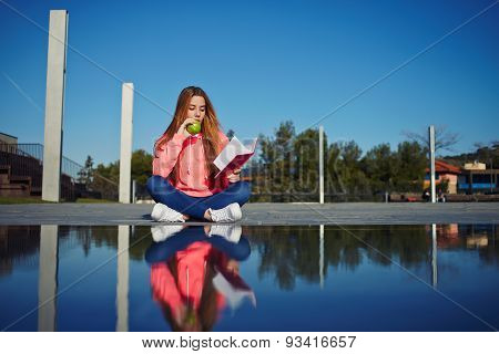 Attractive young woman enjoy her holiday while read literature outdoors at the campus