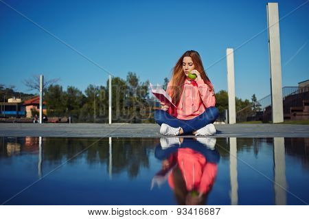 Female student sitting outdoors and reading a book while relaxing on her holiday in the park
