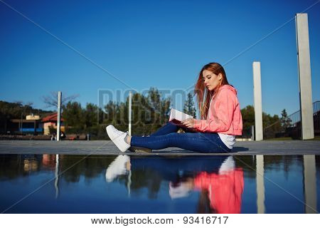 Attractive young woman relaxing on her holiday while read literature outdoors, student on the campus