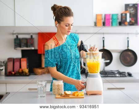 Fit Woman In Workout Gear In Kitchen Making A Smoothie