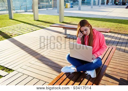 Portrait of beautiful girl sitting on a bench in the street and thoughtfully working on his laptop